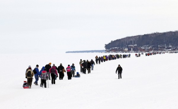 Sightseers trek across a frozen expanse of Lake Superior to the sea caves of the Apostle Islands National Lakeshore